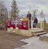 Titre original :  [Men and women seated on small stage behind John G. Diefenbaker speaking at podium during northern tour of Canada, Inuvik].