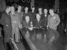 Original title:  Newfoundland and Canadian Government delegation signing the agreement admitting Newfoundland to Confederation. Prime Minister Louis S. St. Laurent and Hon. A.J. Walsh shake hands following signing of agreement.