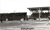 Original title:  Courtesy of Saskatoon Public Library. May 14, 1914. Postcard of Saskatoon's professional team, the Quakers, playing baseball against Regina in Saskatoon's new ball park, Cairn's field. The grandstand can be seen in background with 6404 people in attendance.