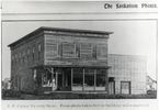 Original title:  Courtesy Saskatoon Public Library. Half-tone (screened) image of J.F. Cairns Grocery Store at 2nd Avenue and 21st Street. This view show front and (North) side view of the frame building, which had a glass store front on the main floor. [ca. 1903]