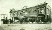 Original title:  Courtesy Saskatoon Public Library. Street view of J.F. Cairns Store, 204-222 2nd Avenue South (near corner of 21st Street), next to corner he sold to Bank of Commerce. Lined up in street are nattily dressed men with horses and buggies. [before July 1912] Creator/Photographer:	McKenzie, Peter.
