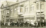 Original title:  Courtesy Saskatoon Public Library. Crowd in front of J. F. Cairns store on 2nd Avenue South admire passing automobiles. between 1906 and 1912