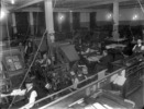 Original title:  Interior view of the Montreal Star Composing Room showing men busy at multiple work stations and manager seated at desk.