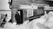 Original title:  Western Canada Airways' first office at Hudson. The man in the doorway is J.A. McDougall, Treasurer of Western Canada Airways.