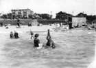 Original title:  Photograph shows Joe Fortes teaching a woman to swim. Other bathers, and West End buildings, can be seen in the background. Creator: Timms, Philip T. (September 16, 1874 – August 8, 1973)