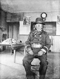 Original title:  Chiniki, head chief of the Stoneys, in classroom at Morley mission, Alberta. Date: [ca. 1896-1906]. Photographer/Illustrator: Walsh, Margaret Ann, Morley, Alberta. Image courtesy of Glenbow Museum, Calgary, Alberta.