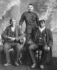 Original title:  L-R: unknown; Sergeant K. J. Anderson; Moostoos [Mostos], Cree chief. Date: c. 1904. Image courtesy of Glenbow Museum, Calgary, Alberta.