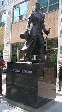 Original title:  Alexander Wood (merchant) - Wikipedia. Statue of Alexander Wood at the corner of Church and Alexander streets in Toronto - photo by user Bearcat (https://en.wikipedia.org/wiki/Alexander_Wood_(merchant)#/media/File:Alexander_Wood_Statue_2005.jpg). Used under  Creative Commons Attribution-ShareAlike 3.0 Unported (CC BY-SA 3.0) https://creativecommons.org/licenses/by-sa/3.0/.