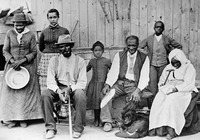 "Original title:    Description Harriet Tubman (c. 1820 – March 10, 1913), far left, with slaves she helped rescue, during the American Civil War. Left to right: Harriet Tubman; Gertie Davis   (adopted daughter of Tubman} behind Tubman; Nelson Davis (husband and 8th USCT veteran); Lee Cheney (great-great-niece); ""Pop""   Alexander; Walter Green; Blind ""Aunty"" Sarah Parker; Dora Stewart (great-niece and granddaughter of Tubman's brother Robert Ross aka John Stewart). [Note: Dora Stewart is sometimes cropped out of other versions of this photograph] Source: Kate Clifford Larson Date Catherine Clinton (2004) gives the date as c. 1885 Source Bettman/Corbis, through The New York Times photo archive, via their online store, here Author Not given Permission (Reusing this file) Public Domain"