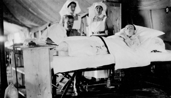 Original title:  Wounded World War Canadian soldier in No. 2 Hospital, with visitor and attending nurses.