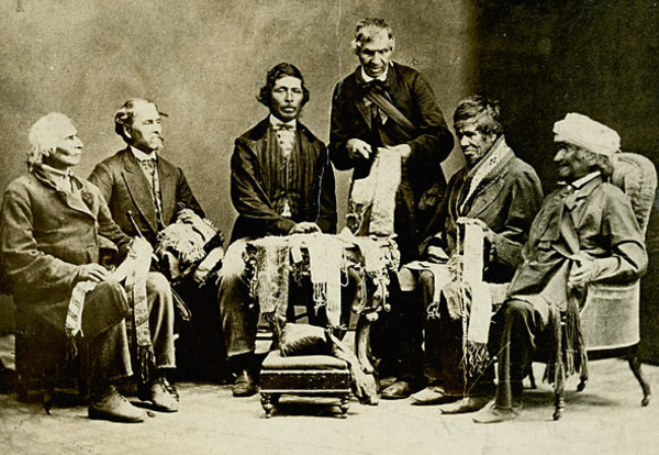 "Titre original :    Description English: Chiefs of the Six Nations at Brantford, Canada, explaining their wampum belts to Horatio Hale September 14, 1871. Image shows Joseph Snow (Hahriron), Onondaga Chief;George H. M. Johnson (Deyonhehgon), Mohawk chief, Government interpreter and son of John Smoke Johnson; John Buck (Skanawatih), Onondaga chief, hereditary keeper of the wampum; John Smoke Johnson (Sakayenkwaraton), Mohawk chief, speaker of the council; Isaac Hill (Kawenenseronton), Onondaga chief, fire keeper; John Seneca Johnson (Kanonkeredawih), Seneca chief. Hale inscribed these photographs, which he sent to colleagues, ""The wampum belts were explained to me on the reserve, at the residence of Chief G. H. M. Johnson; and at my request the chiefs afterwards came with me to Brantford, where the original photograph . . . was taken.--H. Hale, Clinton, Ont."" This copy of the photographs was one tha"
